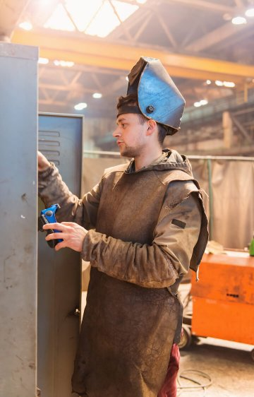Young man in a welding factory in protective workwear